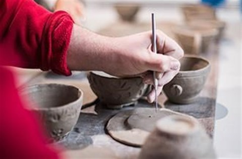 Person working on a pottery piece