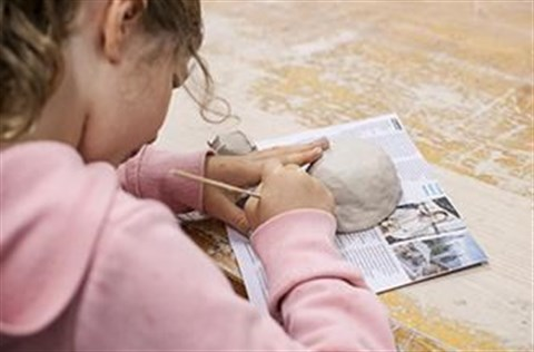 Young girl creating a pottery piece