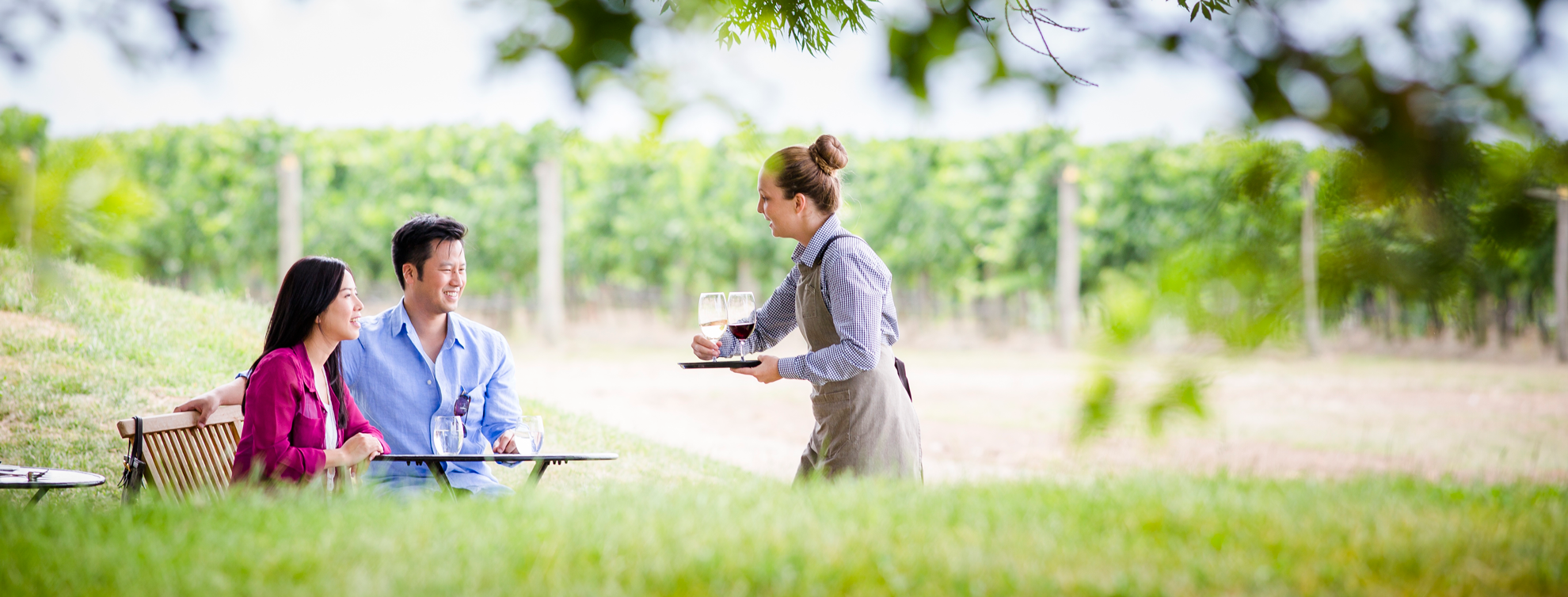 Couple being served wine at a winery in the valley