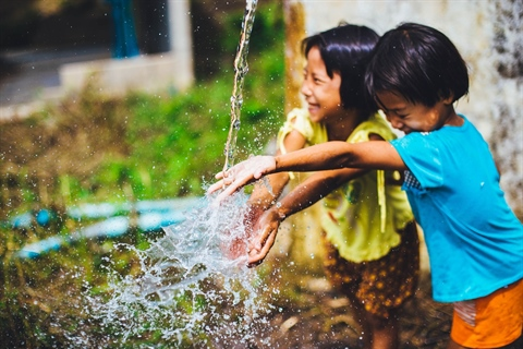 Two children play with water