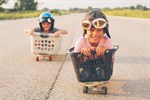 Children in racing on carts made of baskets and skateboards