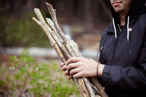 A person holding bundled sticks/branches.