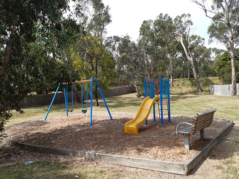 A ground-level photo of the playspace in Carmen Reserve - including swings, slide and a seat.
