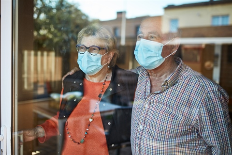 Two older adults look through a window, while wearing face masks.