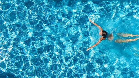 A person swimming in a pool, photo taken from overhead.
