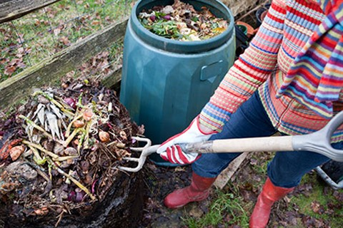 Person turning over compost with a garden fork