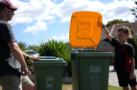 Man and young boy putting recycling in the bin